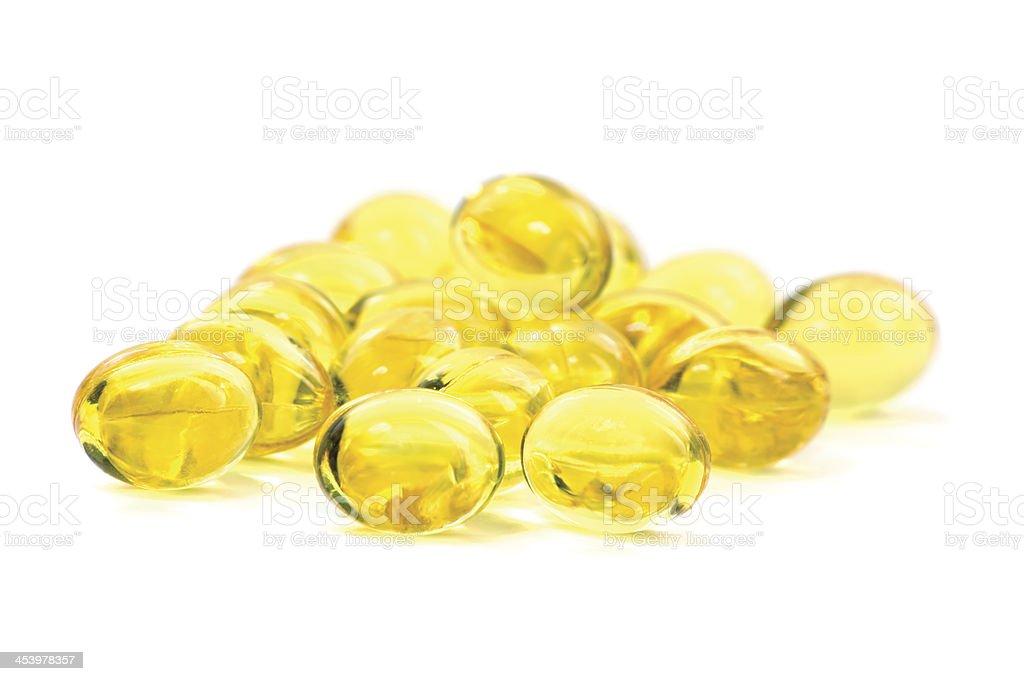 Yellow vitamin fish oil capsules, macro closeup golden pills, isolated stock photo