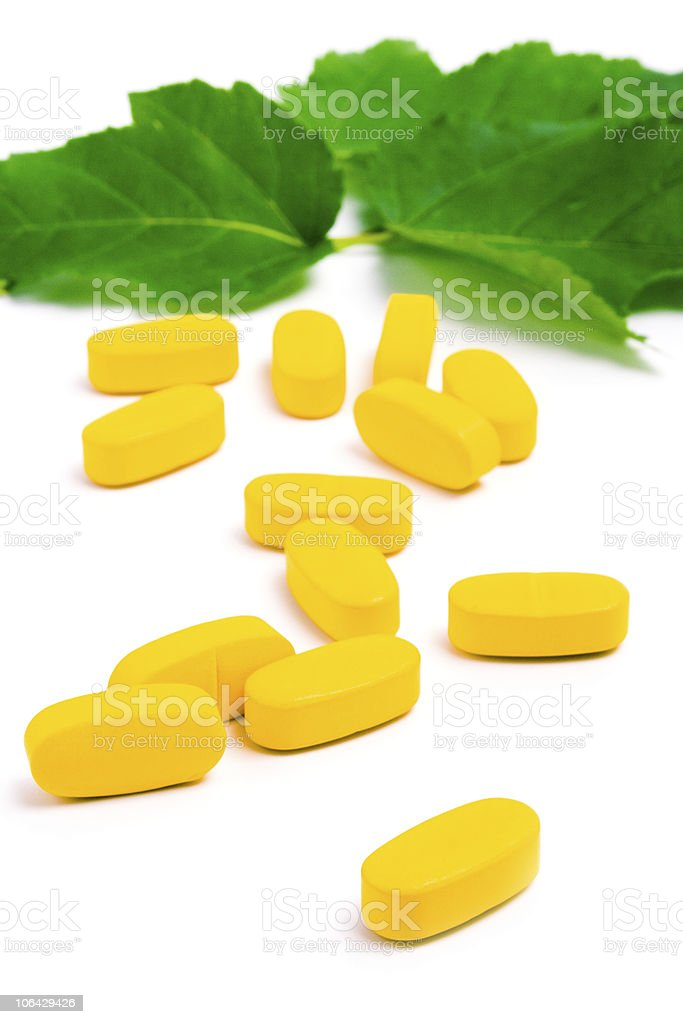 yellow vitamin pills over green leaves royalty-free stock photo