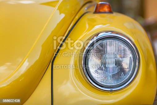 Sigtuna, Sweden - July 6, 2016: Front detail of a yellow classic Volkswagen Beetle standing on parking lot. The beetle was produced by Volkswagen between 1938 and 2003.