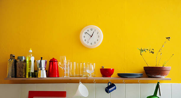 yellow wall clock in the kitchen - yellow stock photos and pictures