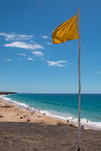 Yellow warning flag on the beach.