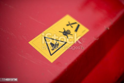 istock Yellow warning label on a red lawn mower 1146919796