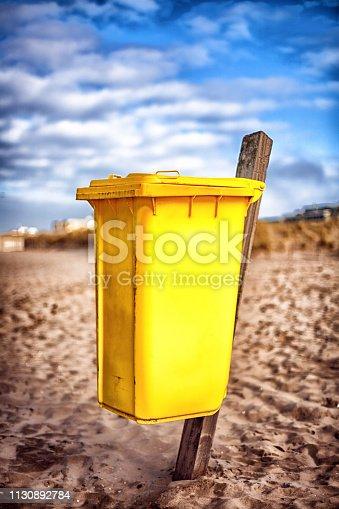 Gele afvalcontainer op het strand