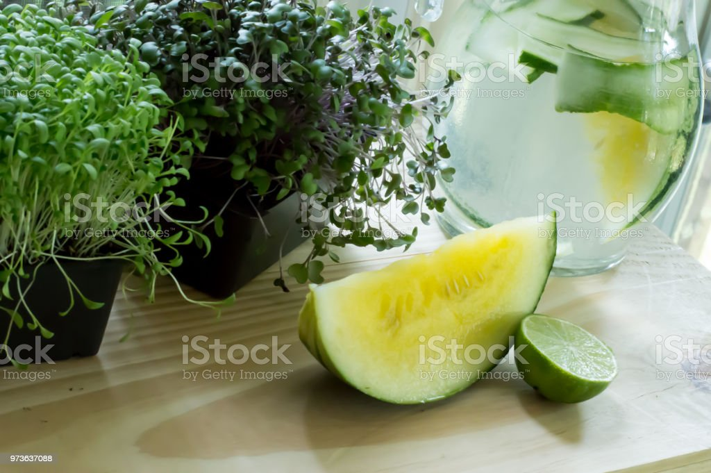 Yellow watermelon slice next to pitcher of fresh detox water with cucumber and  sprouts on wood table stock photo