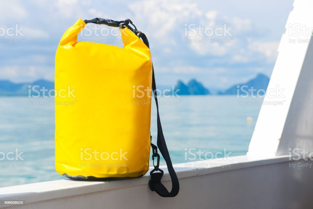 yellow waterproof bag for travel at the sea stock photo