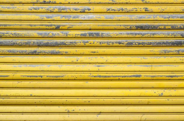 gelb verwitterte metallic-roll-tür. rusty eisen tor. - alu zaun stock-fotos und bilder