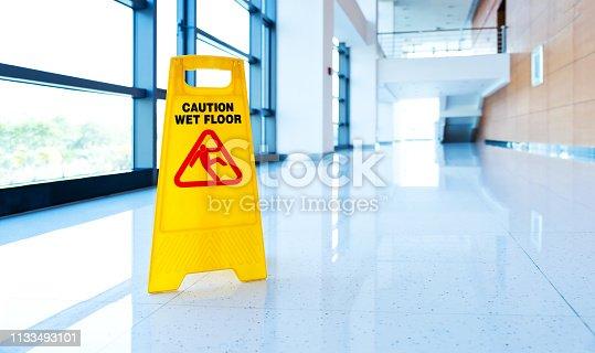 Yellow wet floor warning sign on an office floor