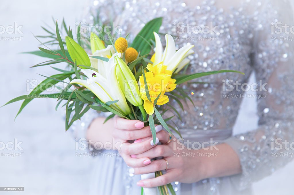 yellow white bouquet of lilies in hands of woman stock photo