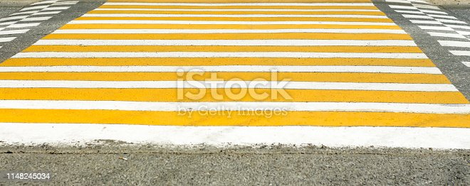 yellow white pedestrian crossing on the city road.