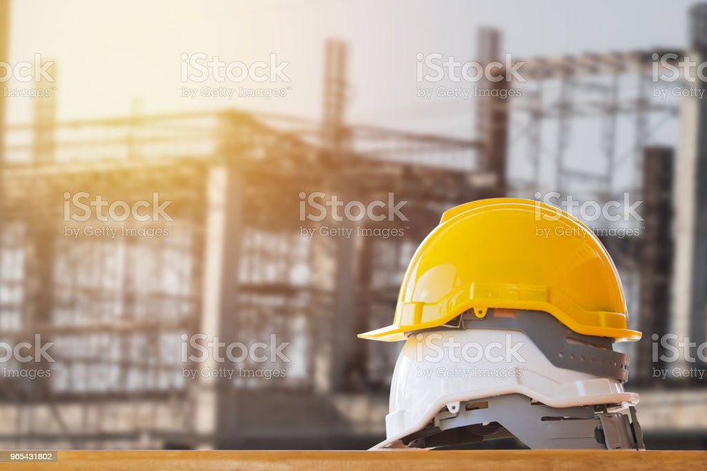 yellow with white safety helmet on table in construction site - Zbiór zdjęć royalty-free (Architektura)