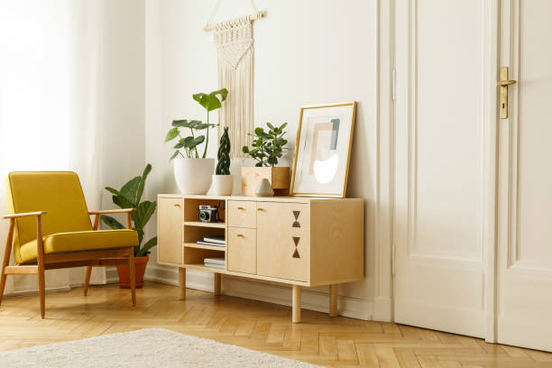 yellow wooden armchair next to cupboard with plants and poster in retro flat interior. real photo - sideboard imagens e fotografias de stock