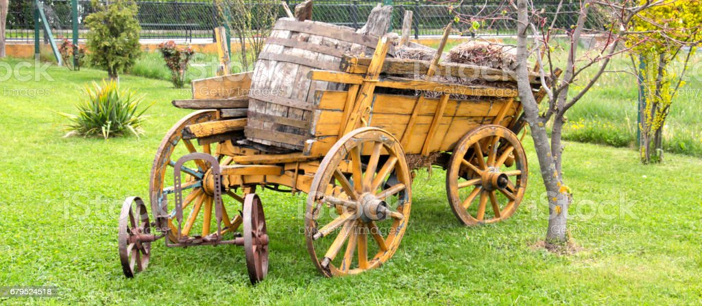 yellow wooden wagon with painted wheels. royalty-free stock photo