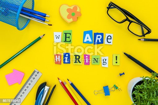 istock WE ARE HIRING CONCEPT ON yellow work place, office background with supplies 857519542