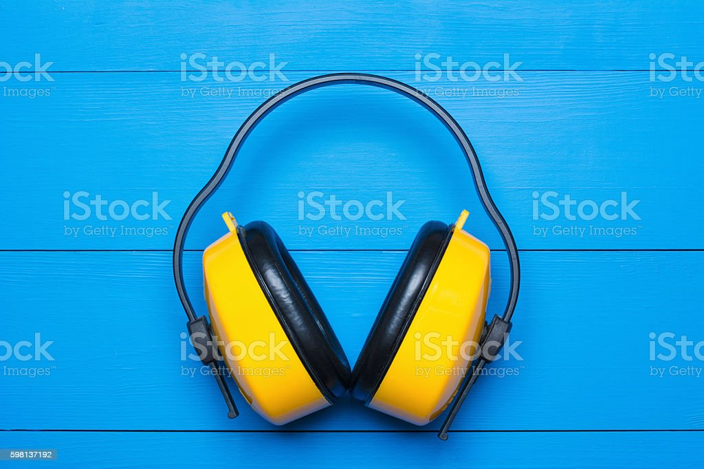 Yellow working protective headphones on painted blue wooden tabl stock photo