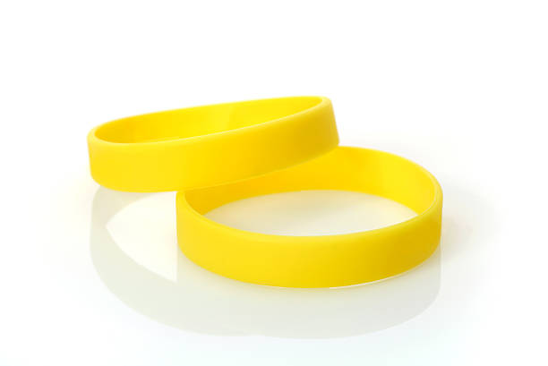 Yellow Wristband Two Yellow Wristbands silicon stock pictures, royalty-free photos & images