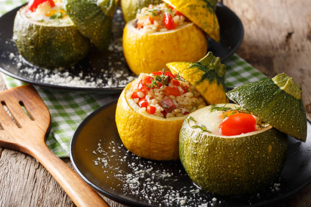 Yellow zucchini baked with bulgur and meat and green zucchini stuffed with egg close-up. horizontal stock photo