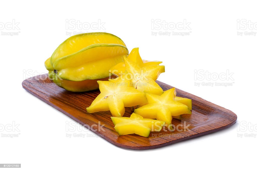 Yellowish green star fruit on the rounded rectangle wooden tray isolated on white background stock photo