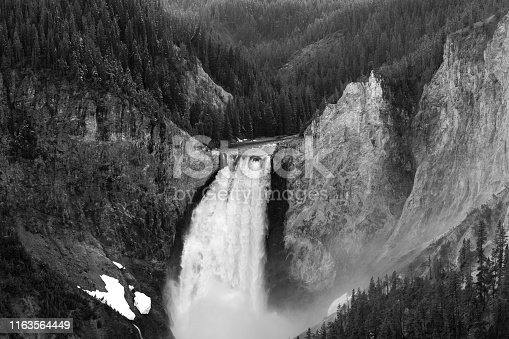 Powerful waterfall in black and white, shot in Yellowstone national park at lookout point.