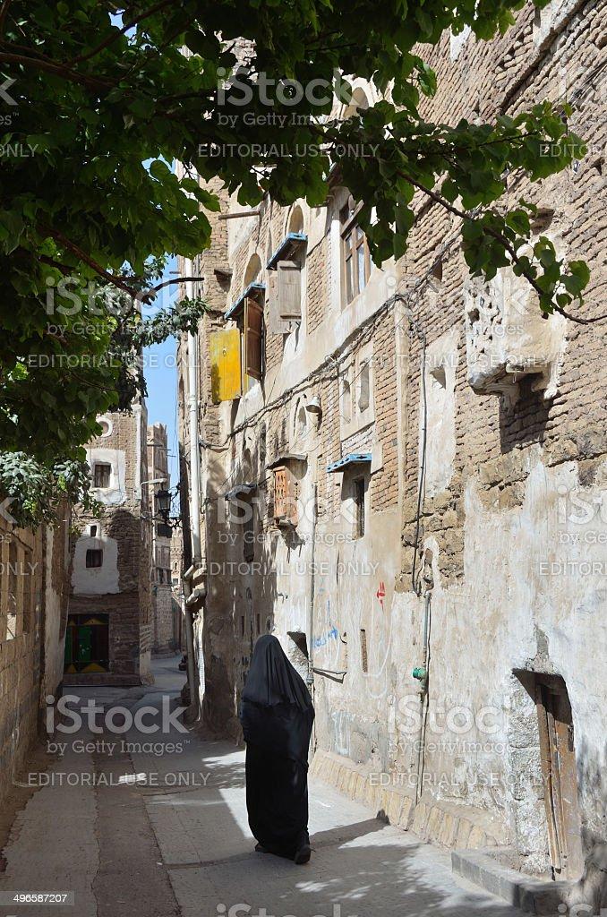 Yemen Scene: Woman walking on ancient street in Sana'a. stock photo