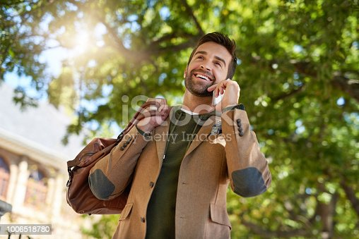 Cropped shot of a handsome young man making a phonecall during his morning commute