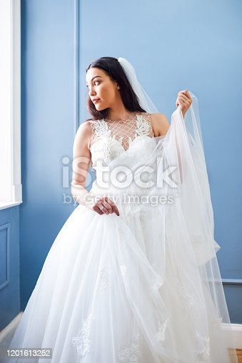 Cropped shot of a beautiful bride wearing her wedding gown in her dressing room