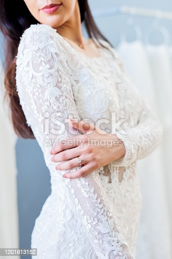 Cropped shot of an unrecognizable bride fitting her wedding gown in a bridal shop