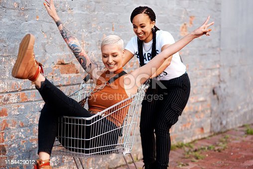 Cropped shot of an energetic young woman pushing her female friend in a shopping cart outdoors