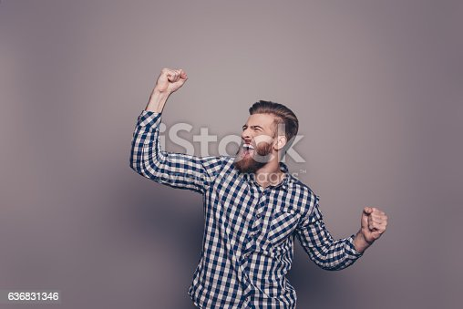 istock Yes, he did it!  happy bearded man raised hands 636831346
