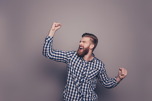 636829368 istock photo Yes, he did it!  happy bearded man raised hands 636831346
