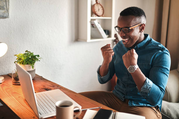 Yes! I did it Cropped shot of a handsome young businessman sitting alone in his home office and feeling excited while using his laptop excited stock pictures, royalty-free photos & images