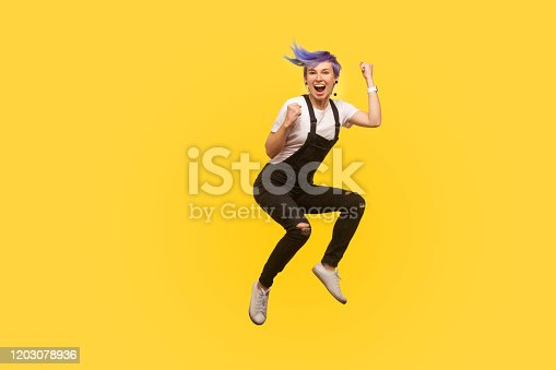 Yes i did it! Portrait of enthusiastic lively hipster girl with violet hair in overalls jumping in air with raised fists, showing yes i did it gesture, life energy. yellow background, studio shot