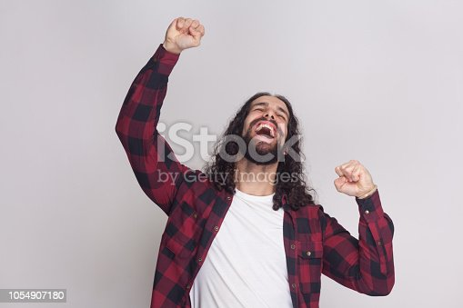 1092211952 istock photo Yes i did it. Successful winner man with beard and black long curly hair in casual checkered red shirt standing, screaming and celebrating his victory. 1054907180