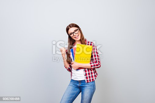 istock Yes! I did it! Young happy lady is gesturing victory with the raised fist, she passed exams in college, standing on pure backgrund in casual outfit 936268488