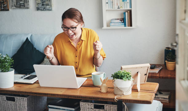 Yes! I got the deal! Cropped shot of an attractive young businesswoman sitting alone in her home office and feeling excited while using her laptop excitment stock pictures, royalty-free photos & images