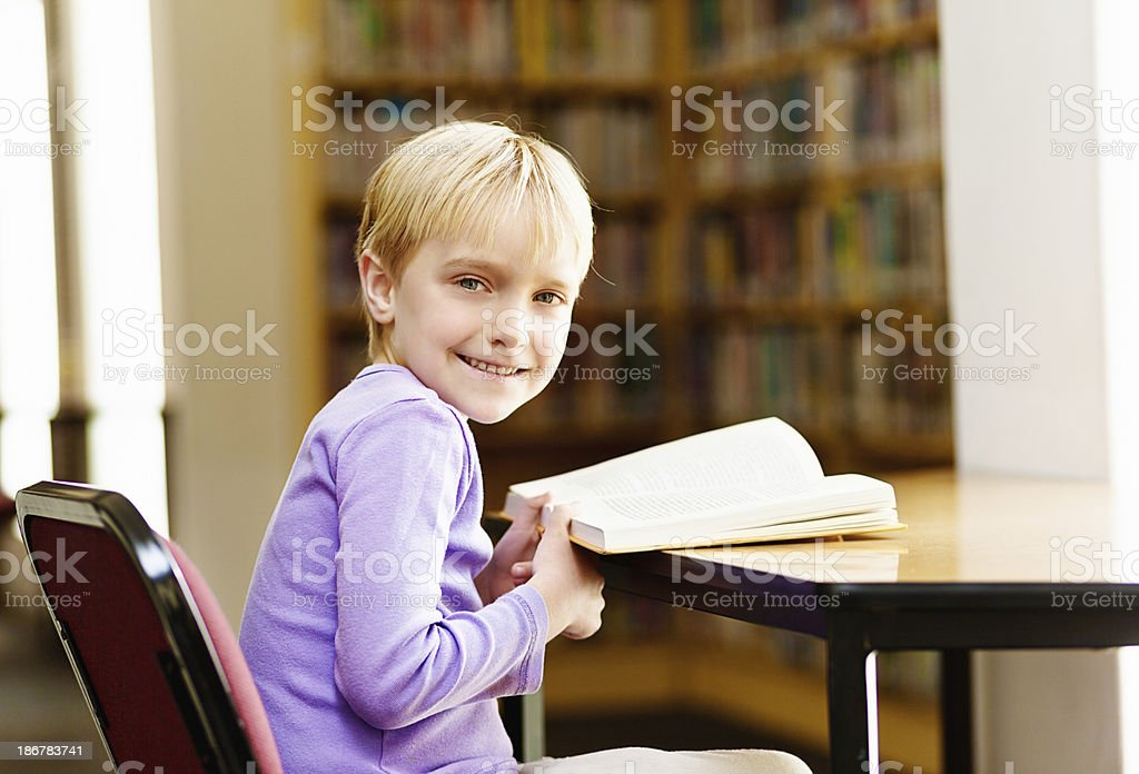 Yes, I love reading, says happy little girl in library royalty-free stock photo