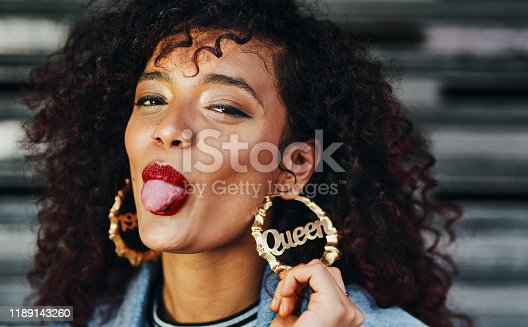 Cropped portrait of an attractive young woman sticking out her tongue while touching her earring which has the word
