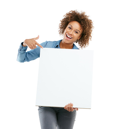 Studio shot of an attractive young woman holding a placard