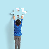 6-7 years old child holding puzzle piece on blue background. His piece complete missing piece on wall.