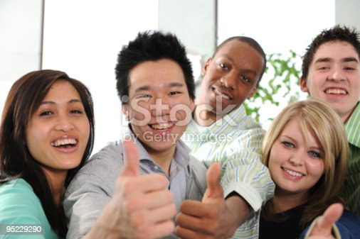 A group of young adults with their thumbs up.
