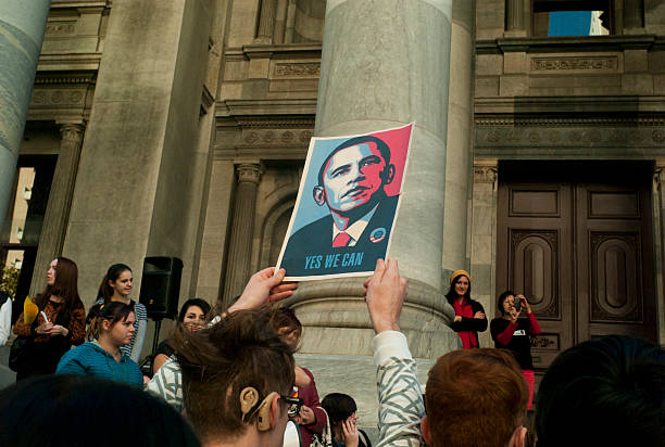 """Yes we can Adelaide, Australia - May 12th, 2012: A man holds up a poster of Barack Obama that says """"Yes We Can"""" during a rally at parliament house for the legalization of same sex marriages  barack obama stock pictures, royalty-free photos & images"""