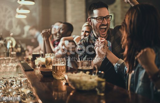 Joyful man celebrating victory of his sports team with his girlfriend in a bar.