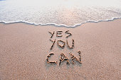 istock yes you can, motivational inspirational message on sand 1003163388