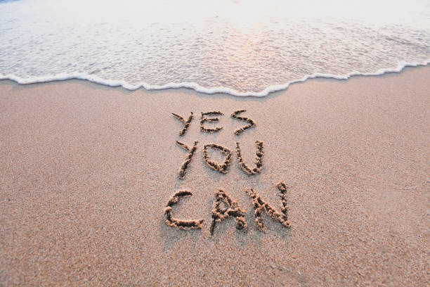 yes you can, motivational inspirational message on sand stock photo