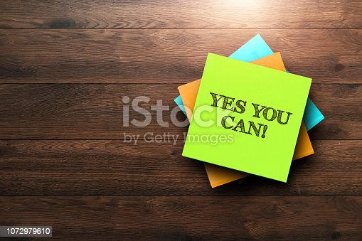 istock Yes You Can , the phrase is written on multi-colored stickers, on a brown wooden background. Business concept, strategy, plan, planning. 1072979610