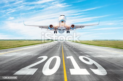 istock Yhe runway 2019 surface of the airport runway texture with take off airplane. Concept of travel in the new year, holidays. 1080835590