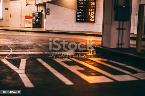 Yield road marker painted on a parking garage asphalt.