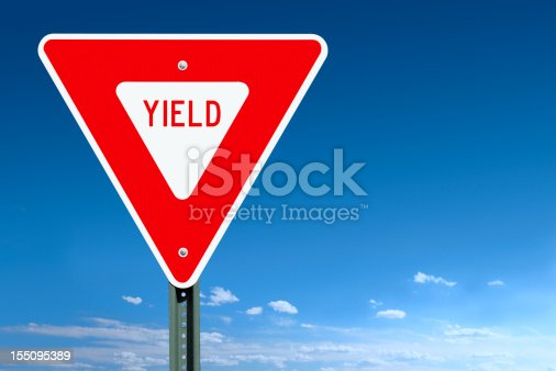 A yield road sign post over a clear blue sky with some clouds at the horizon - a clipping path is included to separate sign from bkg.