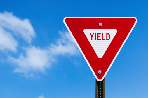 Yield sign and blue sky.