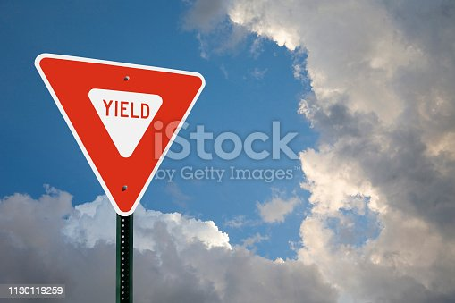A yield sign on the left side of the frame with copy space above and to the right of the sign.  Blue sky and storm clouds in the background.