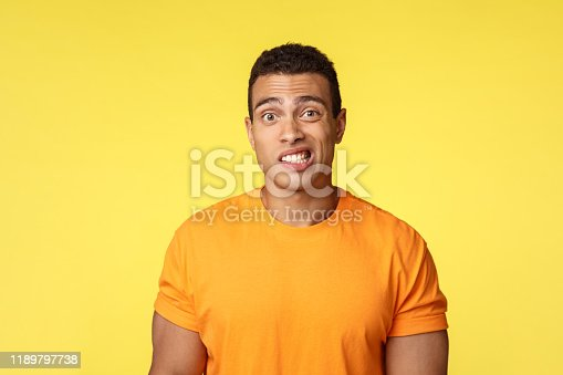 Yikes, awkward. Embarrassed young handsome man caught on lie, feel indesicive and slightly worried, cringe, smiling nervously and look camera with reluctance, stand yellow background.